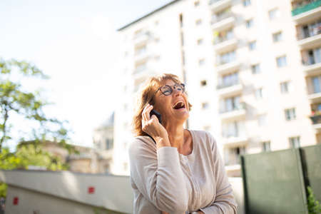 Portrait laughing older woman talking with cellphone outdoors