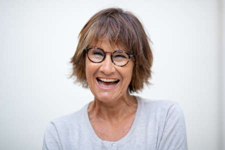 Close up portrait older woman laughing with eyeglasses by white background