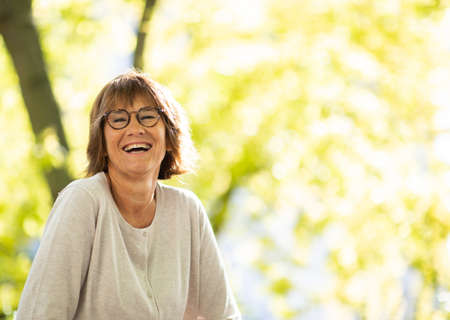 Portrait carefree older woman with glasses laughing outdoors Stockfoto