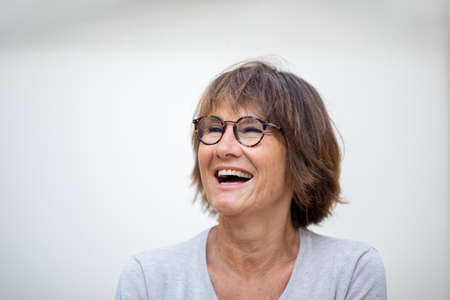 Close up portrait older woman laughing with eyeglasses against white background and looking away
