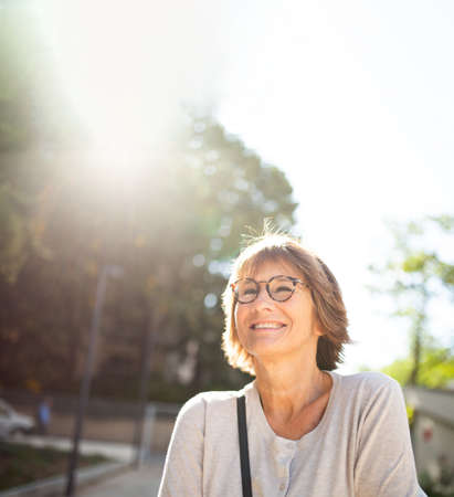 Close up portrait smiling older woman with eyeglasses outside