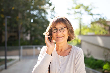 Close up portrait smiling older woman talking with phone outside