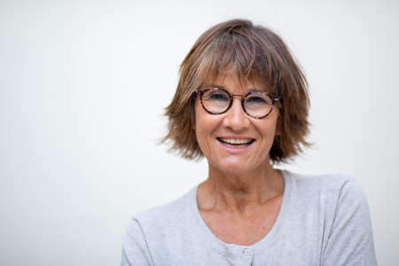 Close up portrait older woman laughing with eyeglasses against white background Stockfoto