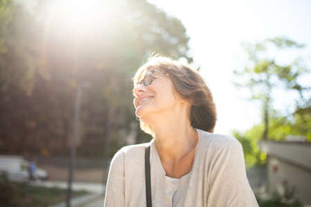 Close up portrait older woman with eyeglasses laughing outside Stockfoto