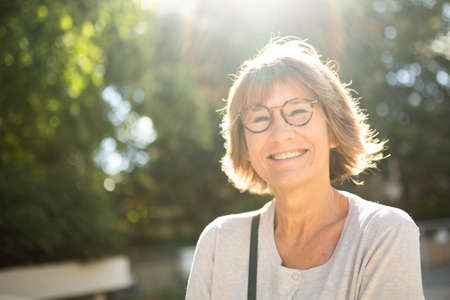 Close up portrait smiling older woman outside with glasses