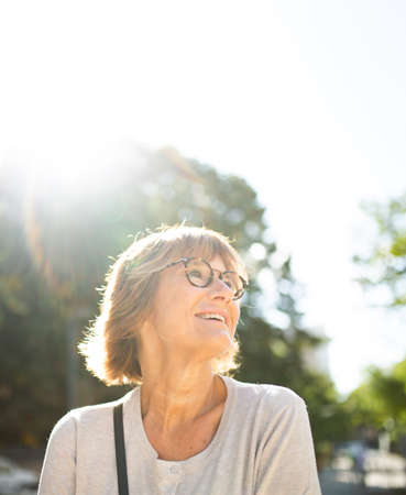 Portrait happy older woman smiling outside on sunny day