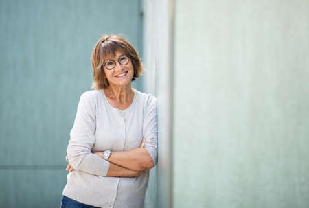Portrait woman in 50s leaning against wall and smiling