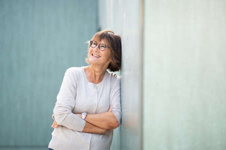 Portrait attractive older woman leaning against wall and laughing Stockfoto