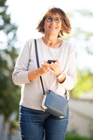 Portrait smiling older woman holding cellphone outdoors