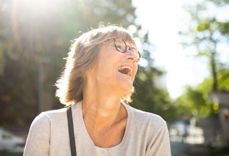 Close up portrait laughing older woman with glasses