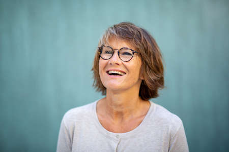 Close up portrait happy woman with glasses laughing by green wall Stockfoto