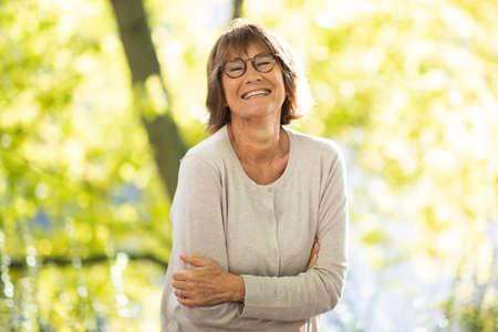 Portrait happy older woman standing in park Stockfoto