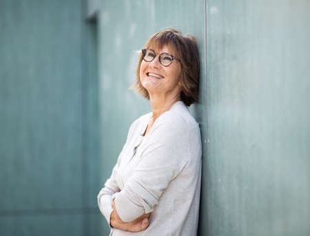 Side portrait happy older woman leaning against wall with arms crossed