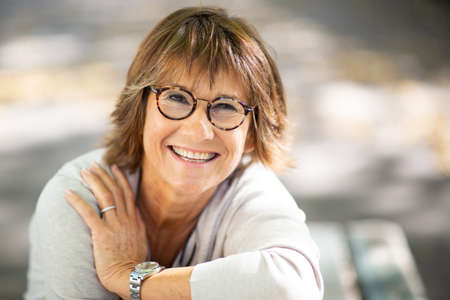 Close up portrait smiling woman with eyeglasses sitting outside Stockfoto