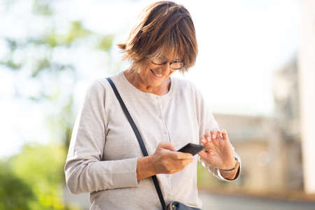 Portrait smiling older woman using mobile phone outdoors Stockfoto