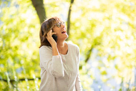 Portrait laughing older woman talking with mobile phone in park