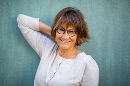 Close up portrait older woman smiling with eyeglasses against green wall