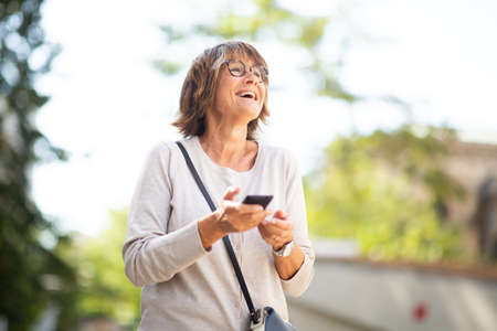 Portrait older woman holding mobile phone and laughing