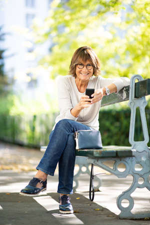 Portrait attractive older woman sitting on park bench with mobile phone