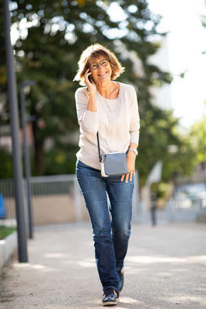 Full body portrait happy woman walking and talking with mobile phone outside