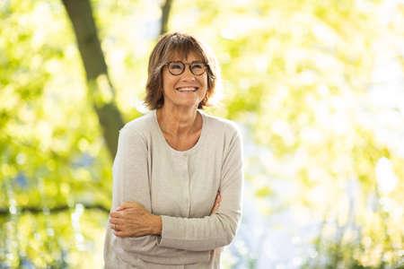 Portrait woman in 60s smiling outside in park