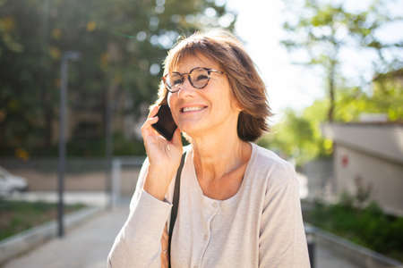 Close up portrait smiling older woman talking with mobile phone outside Stockfoto