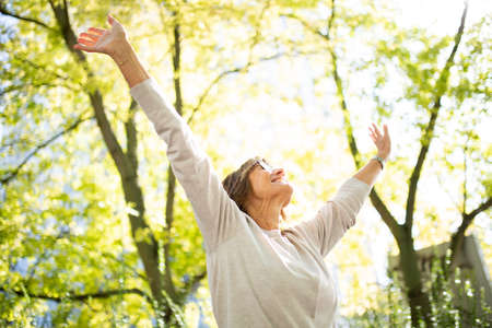 Portrait carefree older woman with arms up in park