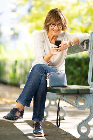Portrait smiling older woman sitting on park bench with mobile phone