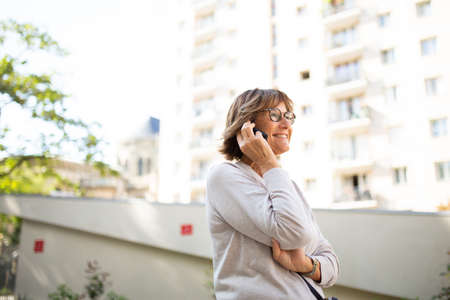 Portrait smiling older woman talking with cellphone outdoors