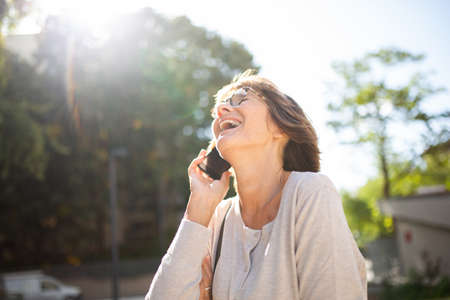 Portrait older woman laughing with mobile phone outside Stockfoto