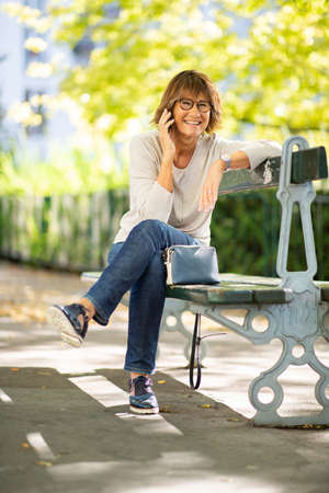 Portrait smiling older woman sitting on park bench talking with phone