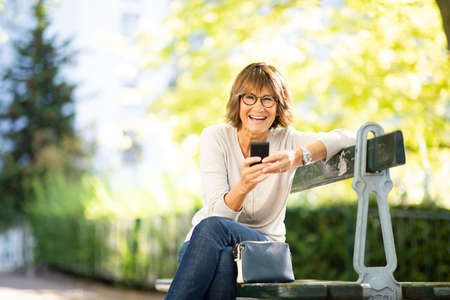 Portrait happy older woman sitting on park bench using cellphone