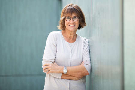 Portrait attractive older woman leaning against wall and smiling Stockfoto