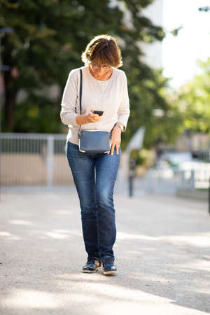 Full body portrait happy woman walking with mobile phone outside