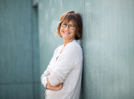 Side portrait smiling older woman leaning against wall with arms crossed