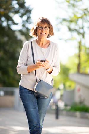 Portrait smiling older woman holding mobile phone outdoors