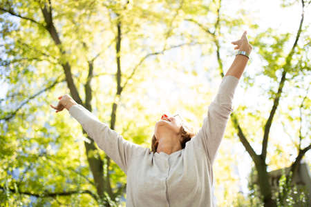 Portrait happy woman with arms outstretched in nature