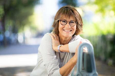Close up portrait smiling older woman sitting on park bench