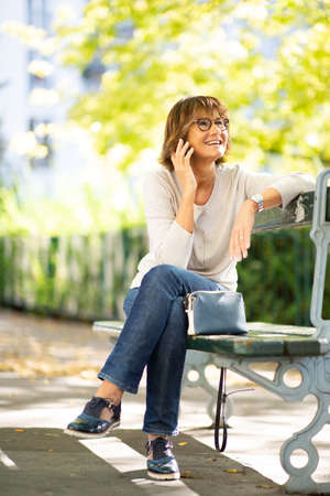 Portrait older woman smiling while talking with mobile phone on park bench Stockfoto