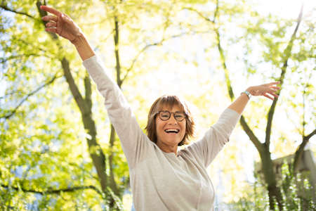Portrait happy older woman with arms outstretched in nature
