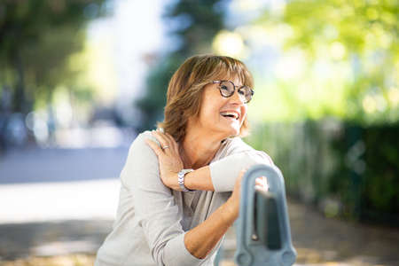 Close up portrait older woman sitting on park bench laughing