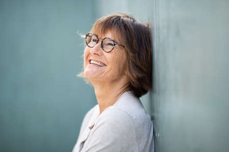 Close up side portrait smiling older woman with eyeglasses leaning against wall