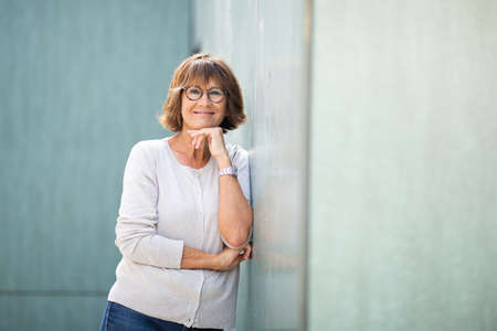 Portrait older woman leaning against wall and smiling Stockfoto