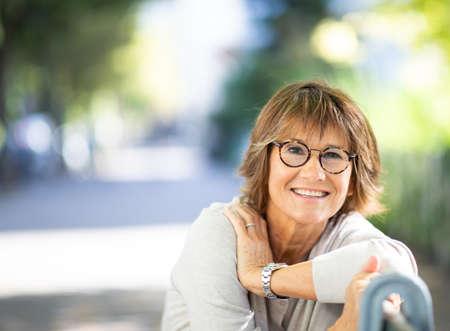 Close up portrait smiling older woman sitting on park bench outside