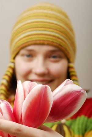 Buds of tulips and girl in yellow cap on background  photo