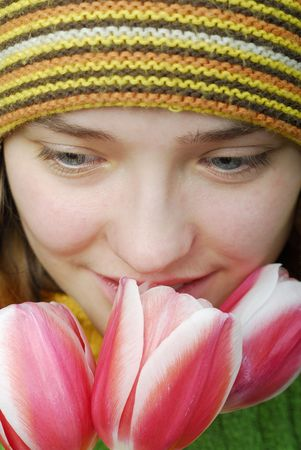 Girl in striped cap and face in pink tulips. photo