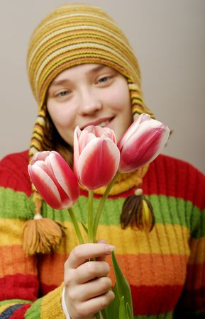 Girl in striped cap with three tulips. photo