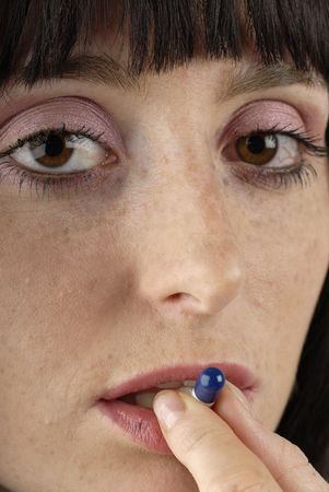 Young woman put pill in her mouth photo