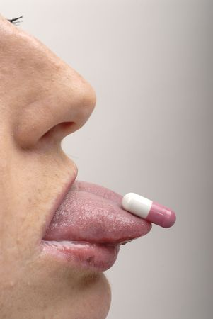 Young woman with pink pill on her tongue photo