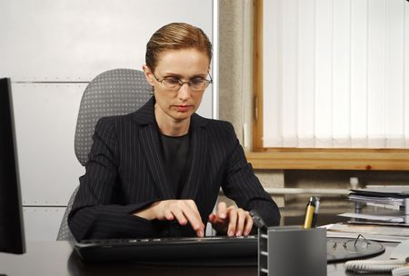 glases: Typeing 40 years old business woman Stock Photo